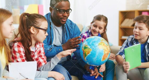 Group of preschoolers studying our planet on globe